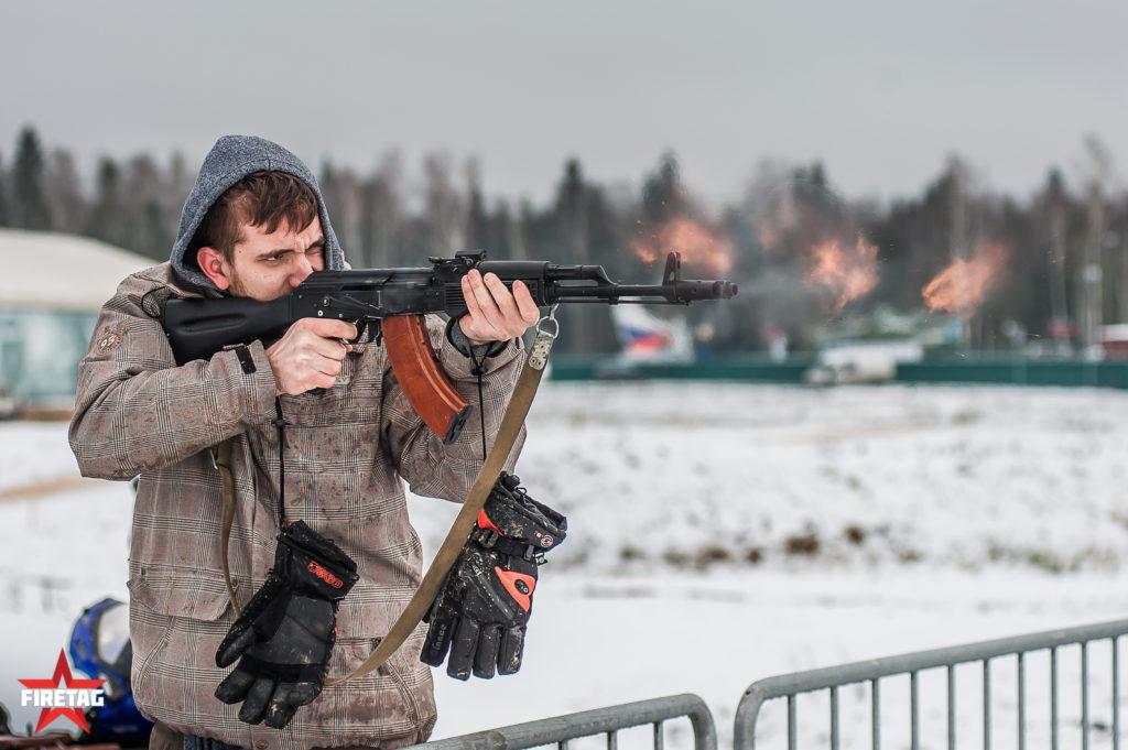 Участник соревнований на огневом рубеже стреляет из фаертаг-автомата Калашникова во время гонки по автобиатлону