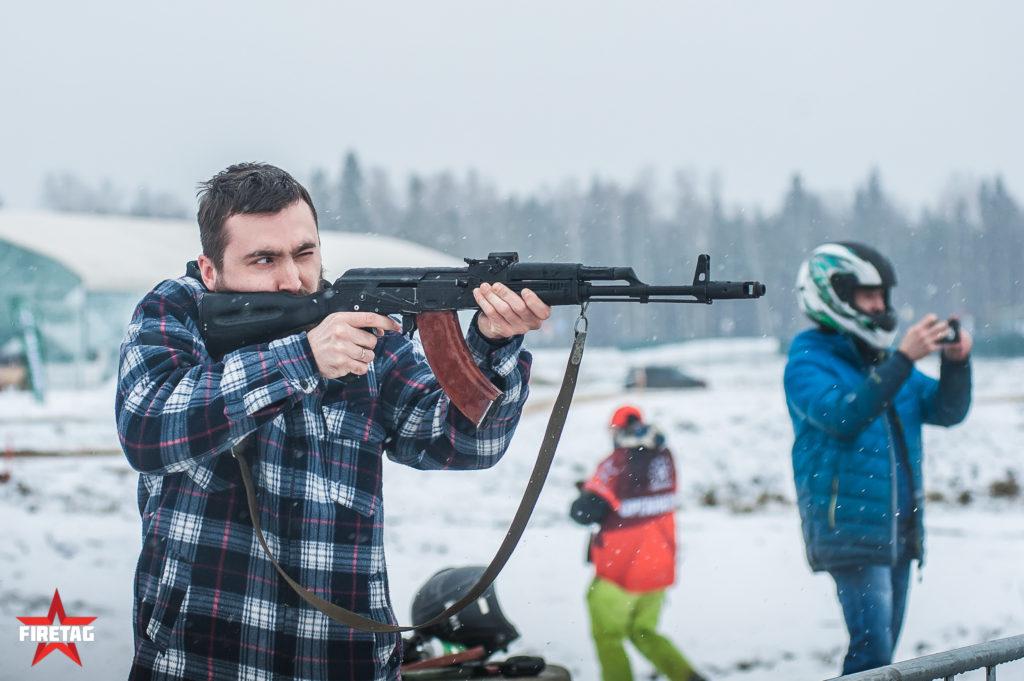 Участник соревнований на огневом рубеже стреляет из фаертаг-автомата