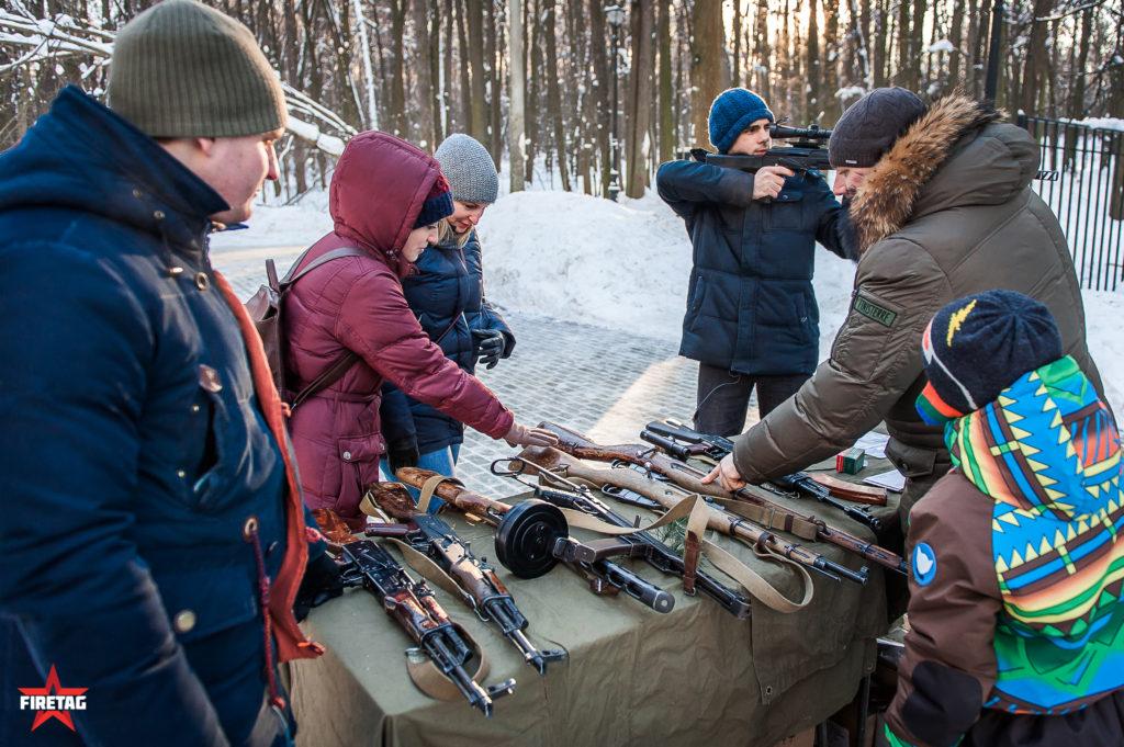 посетители разглядывают оружие в тире
